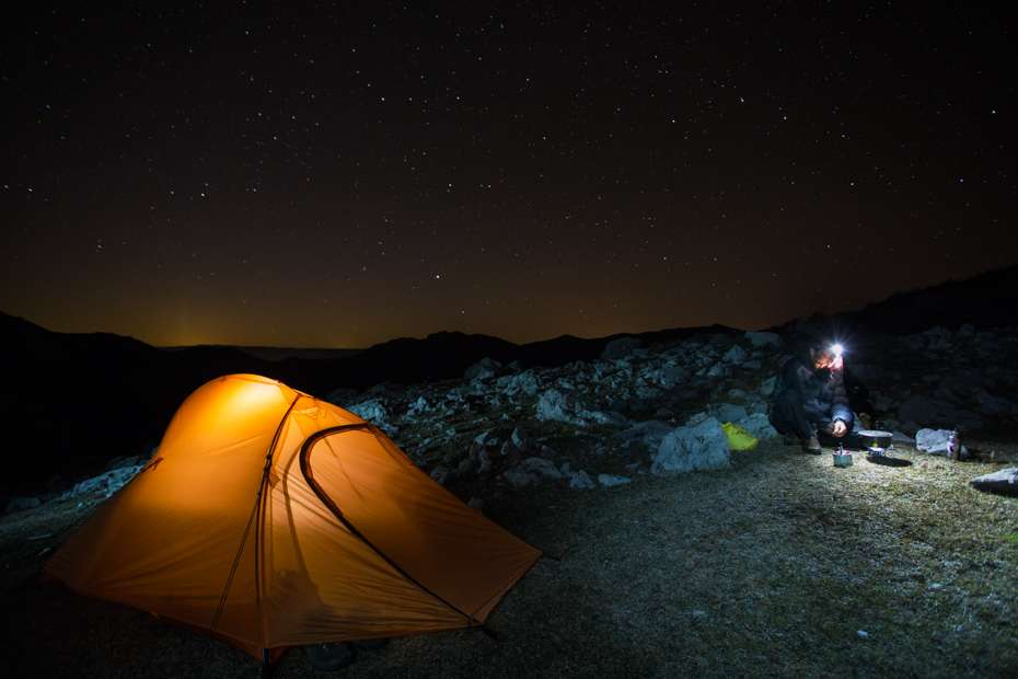 Hiker heating up water beside his tent under starry sky over a rocky limestone ridge in Mehedinti Plateau Geopark, Romania