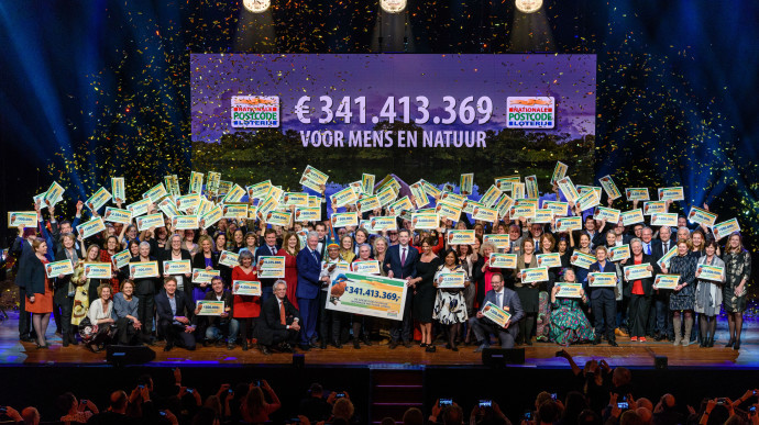 Lucky winners pose on stage with special guest and former US president Bill Clinton at the Annual Charity Gala of the Dutch Postcode Lottery, held on February 6 in Amsterdam.